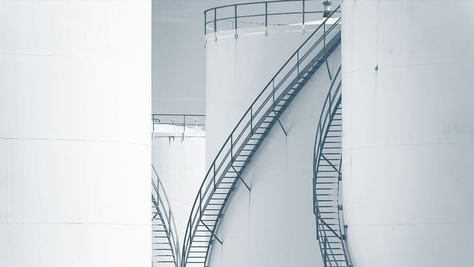 Stairs leading up to several large oil tanks